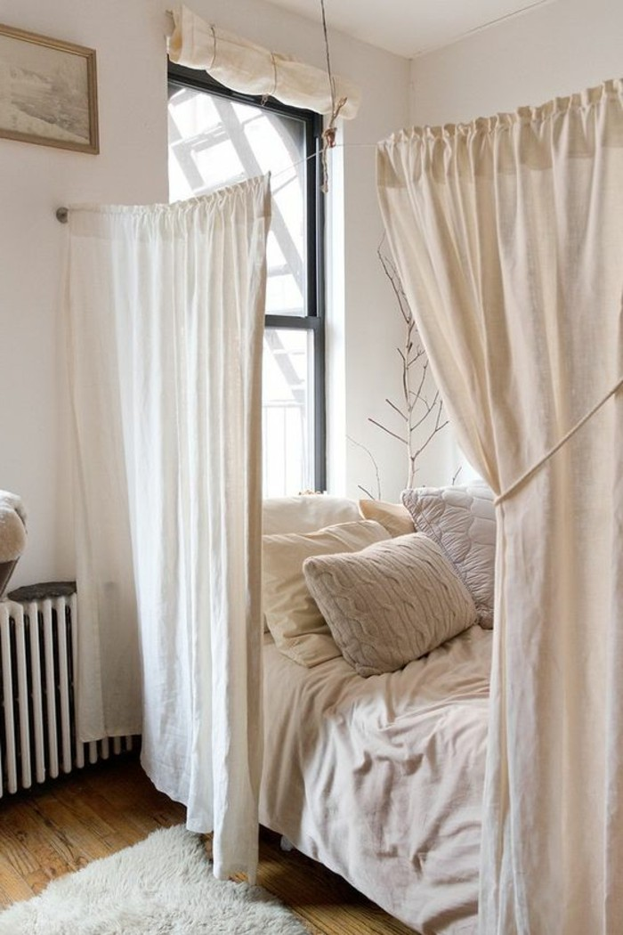 studio apartment ideas, half-drawn ivory-colored curtains, separating a bed from the rest of the room, studio apartment ideas, laminate floor with fluffy off-white rug
