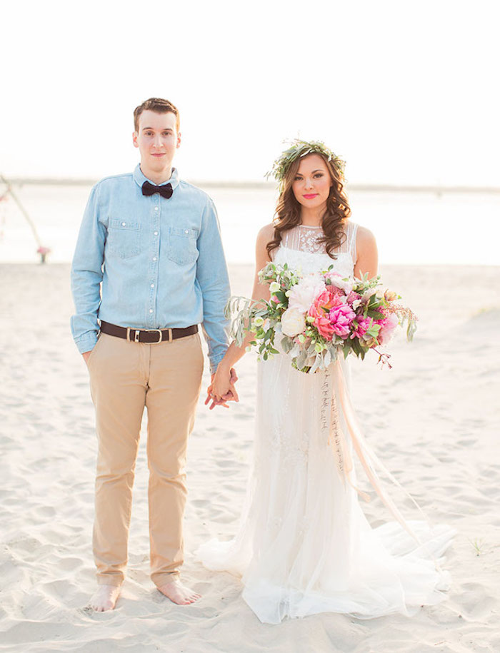 groom in a pale blue shirt, black bowtie and beige pants, holding hands with brunette bride, in a white lace beach wedding dress, holding large multi colored bouquet