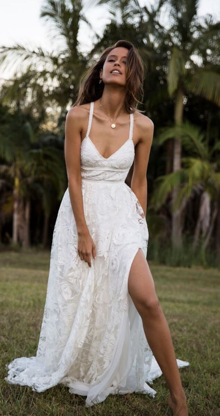 casual beach wedding dresses, young brunette woman, wearing an embroidered white maxi dress, with side slit, revealing her bare leg
