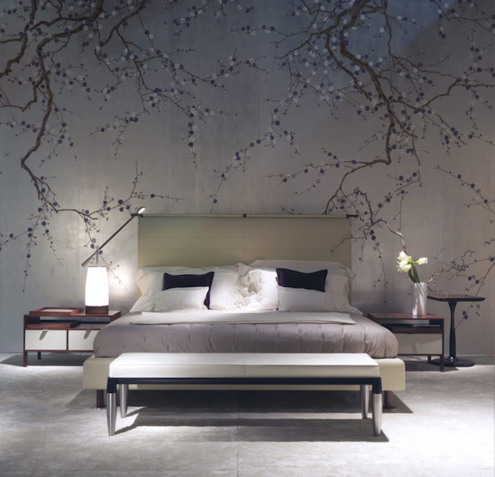 mural depicting tree branches in blossom, on a pale gray wall, near cream-colored bed, bedroom wall decor, white bench and two-tone bedside tables