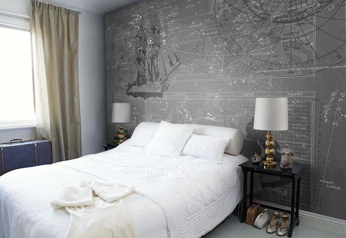 compass and a ship, star maps and constellations, on a grey wallpaper, near a soft white bed, bedroom wall decor, matching bedside tables with identical lamps