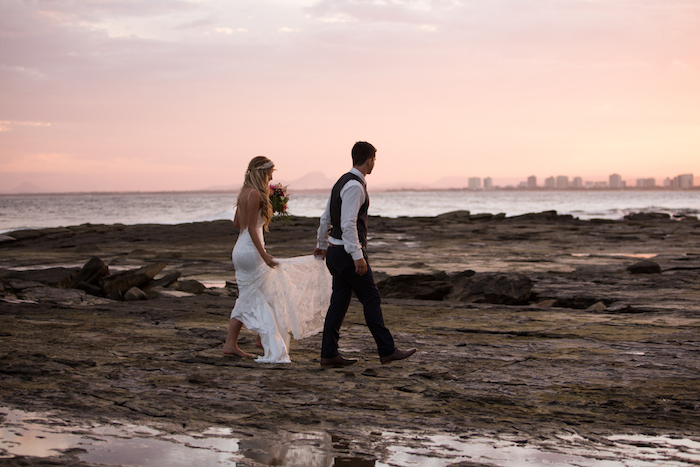 pink sunset sky, beach weddings in florida, barefoot bride in long backless white gown, and groom in black white shirt, black pants and vest, walking on a stony sea shore