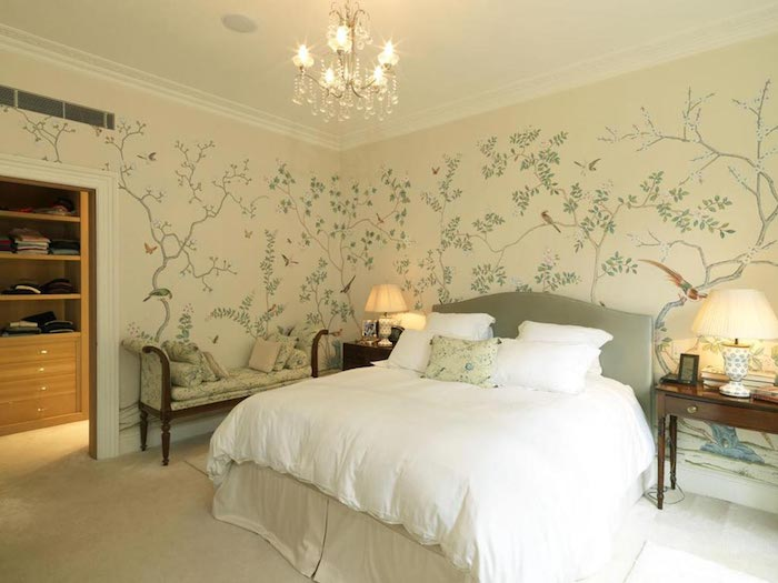delicate botanical wallpaper, in cream and pale green, with thin trees and different birds, decorating the walls of a bedroom, with large fluffy bed