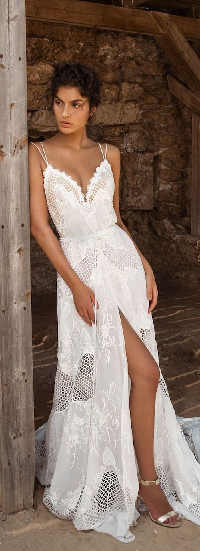 maxi dress in white, with lace inserts and embroidery, featuring thin straps and a slit, casual beach wedding dresses, worn by tanned brunette young woman, with curly dark hair put up, and silver heeled sandals