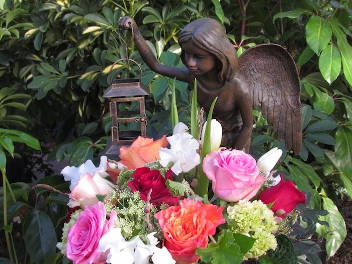 bouquet with pink, red and orange roses, and several white flowers, placed in a garden, near a small angel statue, holding a lantern, fairy garden images, foliage in the background