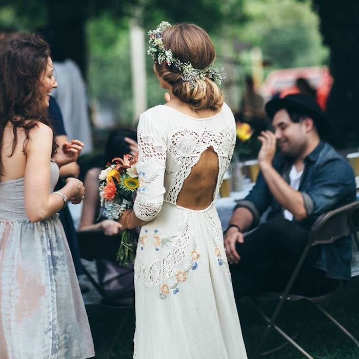embroidered white gown, with lace inserts, cutout back and floral motives, casual beach wedding dresses, worn by bride with light brunette hair, in a messy bun, delicate flower crown