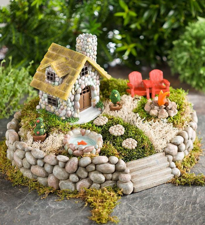 couple of red miniature armchairs, on green and pale beige moss, inside a miniature fairy garden, with tiny house and goldfish pond