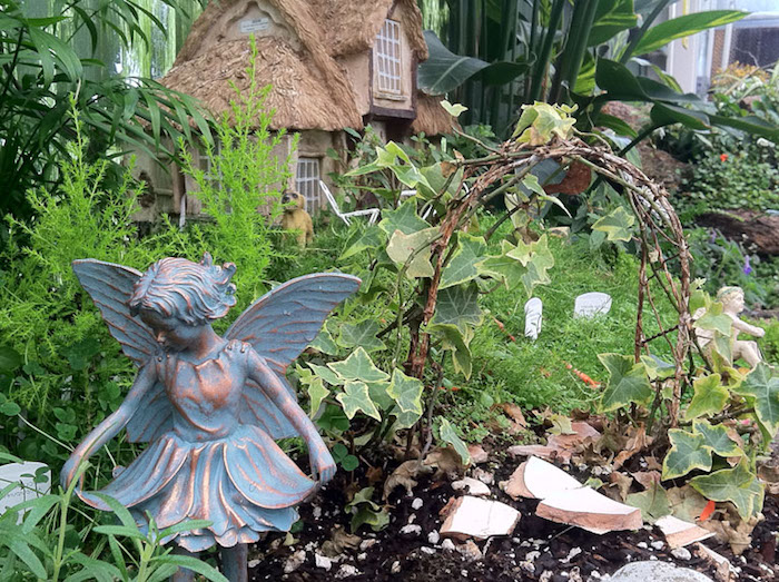 antique metal statue of a fairy, placed near a small arch, made from twigs and ivy, garden with various plants, and a miniature house in the background, fairy garden pictures