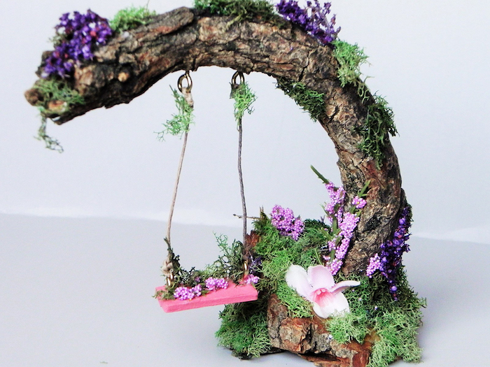 pink miniature swing, hanging from a dried branch, fairy garden pictures, decorated with purple and pink flowers, and green moss