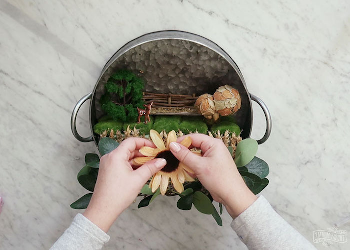 fake sunflower being added to a spring wreath, made from aluminium cooking pot, containing fairy garden, little figurines and wheat stalks, moss and dried mushrooms