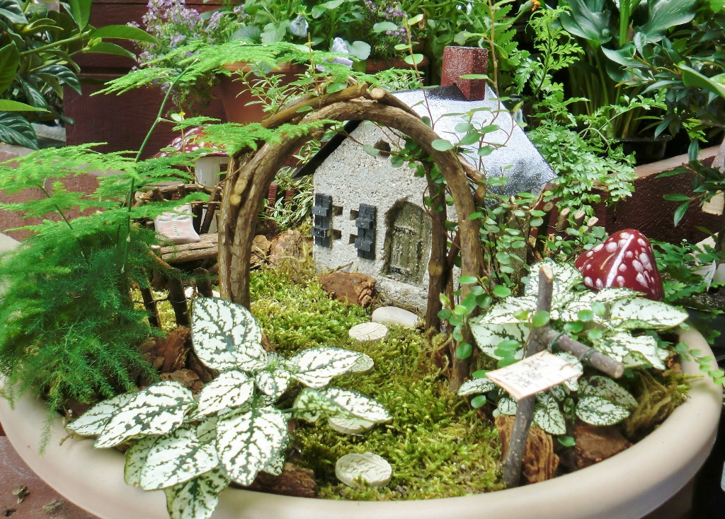 arch made of tiny woven branches, near ferns and other green plants, in a moss covered pot, decorated with a tiny fairy house, and mushroom figurines
