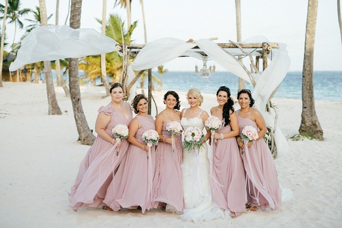 rosy ash pink, floaty bridesmaid dresses, on five women, each holding a small bouquet, standing next to a smiling bride, sea in the background