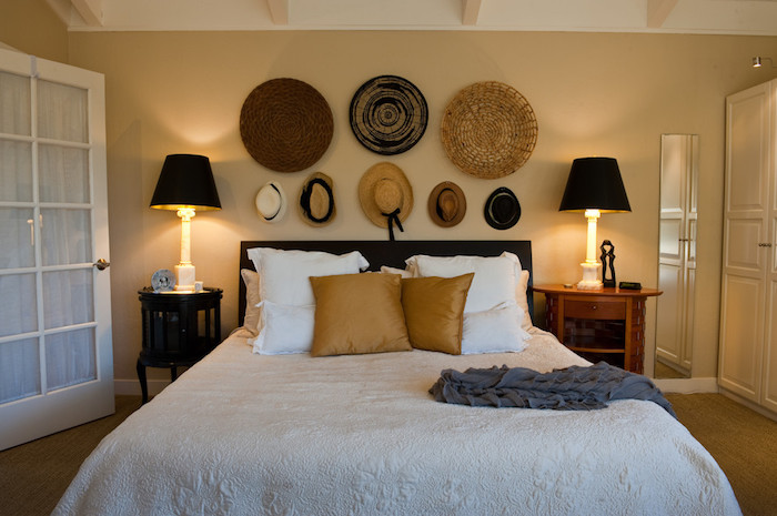 hats and round mats in different sizes and colors, made from straw, decorating a pale yellow wall, near double bed, with two bedside tables, and matching lamps