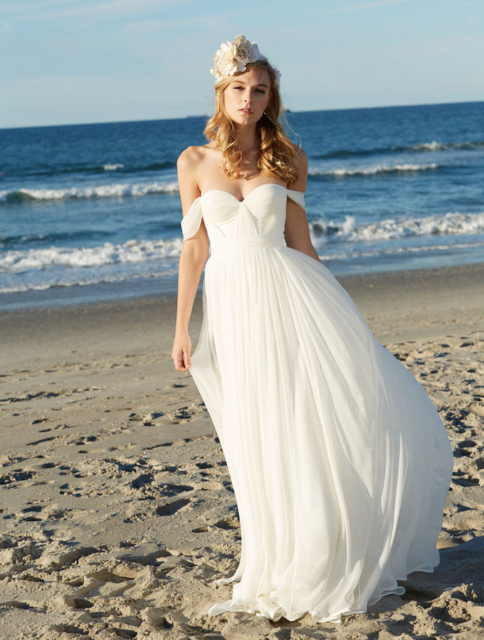 floaty white gown, with slouching shoulder straps, beach wedding dresses, worn by blonde woman with curled hair, and floral hair ornament in cream, standing on a sandy beach
