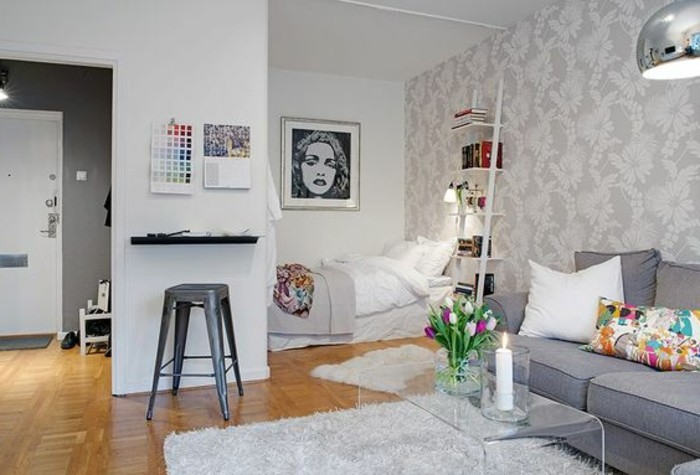artwork of madonna in black and white, hanging over a small bed, in one-room flat, with gray sofa and pale gray rug, how to decorate a studio apartment, laminate floor and glass coffee table