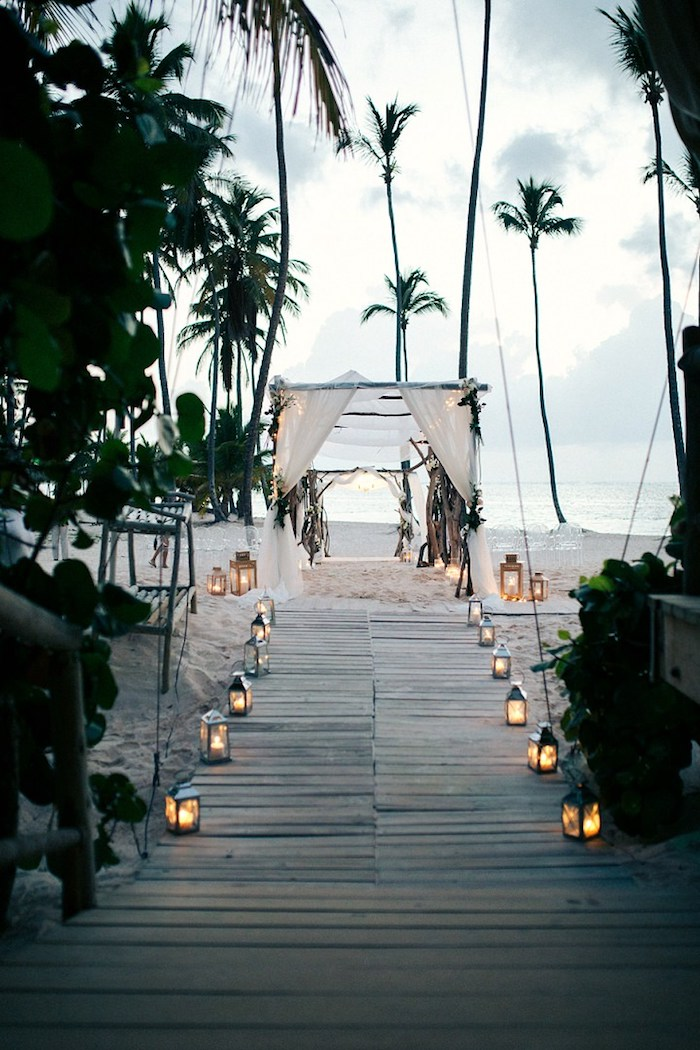 tall palm trees, on a sandy white shore, wooden boards leading to a simple wedding tent, made from wooden poles and white cloth, beach wedding venues, lots of lit lanterns