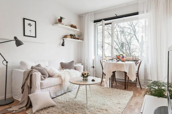 balcony with open door, and sheer white curtains, attached to room decorated in light colors, sofa with several cushions, small apartment living room ideas, cream fluffy rug, round coffee table