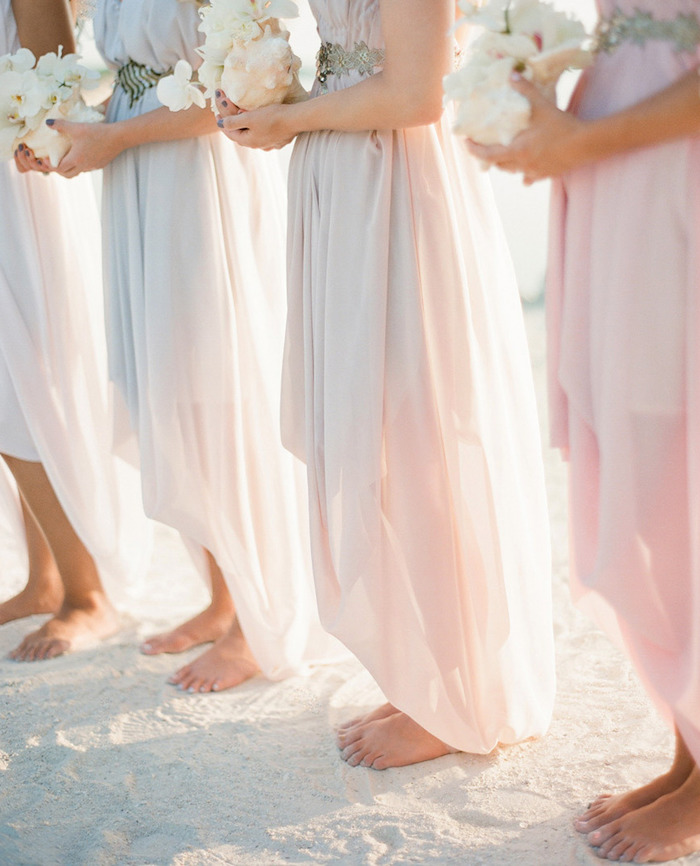 barefoot bridesmaids in pale pink, floaty asymmetrical gowns, with silver belts, each holding a large white conch shell, containing white orchids