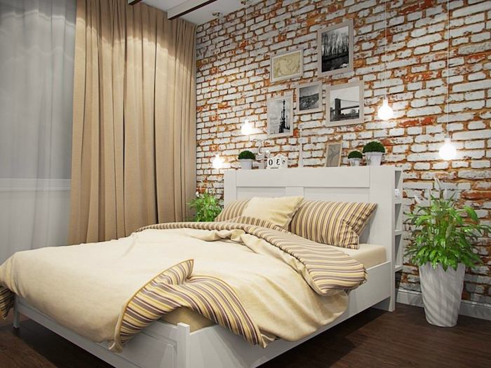 shabby orange and white brick wall, decorated with several framed images, near white bed with pale yellow bedding, wall decor ideas, hanging lights and two potted plants