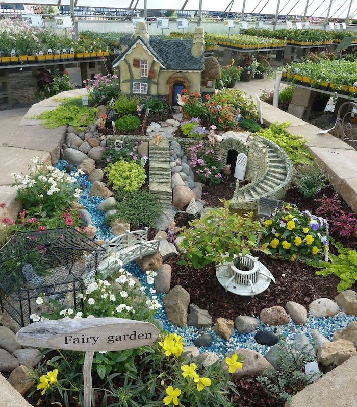 winding stone stairs, of a tiny size, near black wire gazebo, little white bridge, a decorative house, and other ornaments, diy fairy house, in a garden with different flowers, placed inside a large greenhouse