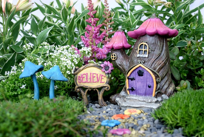 believe written with pink letters, on a board next to a fairy house ornament, made to look like a small tree, with pink flowers roof, two blue mushroom figurines, and many green plants