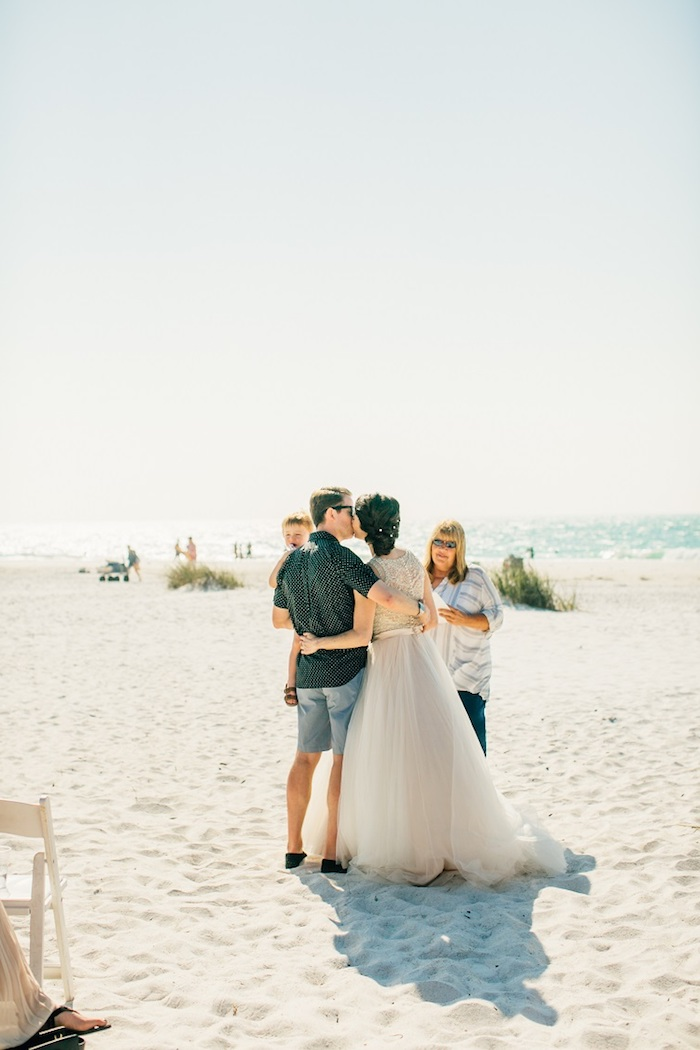 florida destination weddings, kissing couple at the beach, bride in floaty embroidered dress, with tulle skirt, and groom in denim shorts, and dark casual shirt