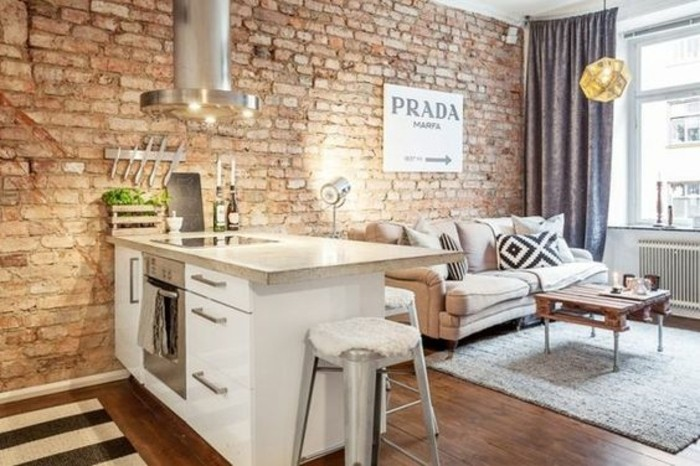 brick wall with industrial feel, inside room with small kitchenette, studio apartment design, off-white sofa and rustic coffee table