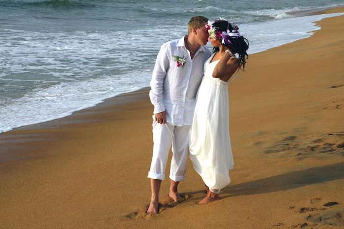 kissing couple dressed in white, floaty grecian gown on a brunette bride, with flowers in her hair, shirt and rolled-up pants on a blonde groom, casual beach wedding dresses