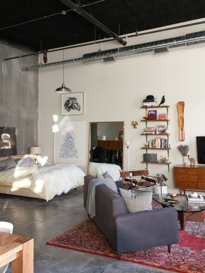 black ceiling with metal pipes and details, in open-plan industrial style home, how to decorate a studio apartment, double bed and dark gray sofa, red patterned kilim rug, bookshelves and decorations