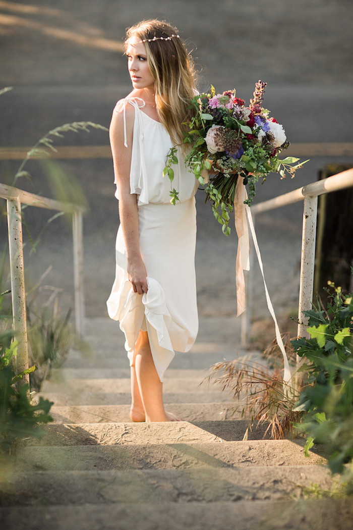 simple white grecian wedding gown, beach wedding dresses, worn by young woman, with delicate flower crown, holding a large bouquet, standing on sandy steps