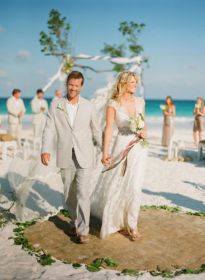 relaxed boho wedding at the beach, happy bride and groom, dressed in a white retro lace gown, and pale gray suit, walking while holding hands