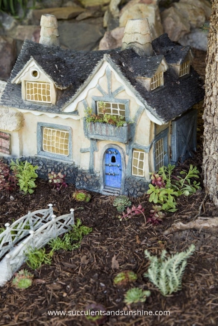 dark blue roof, light blue beams and window frames, and a bright blue door, on a miniature fairy house ornament, placed on a forest floor, near white toy bridge