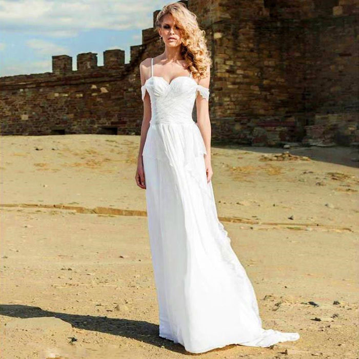 antique castle wall, on a sandy seashore, slim blonde woman with curly hair, wearing white maxi dress, with straps and slouched sleeve details