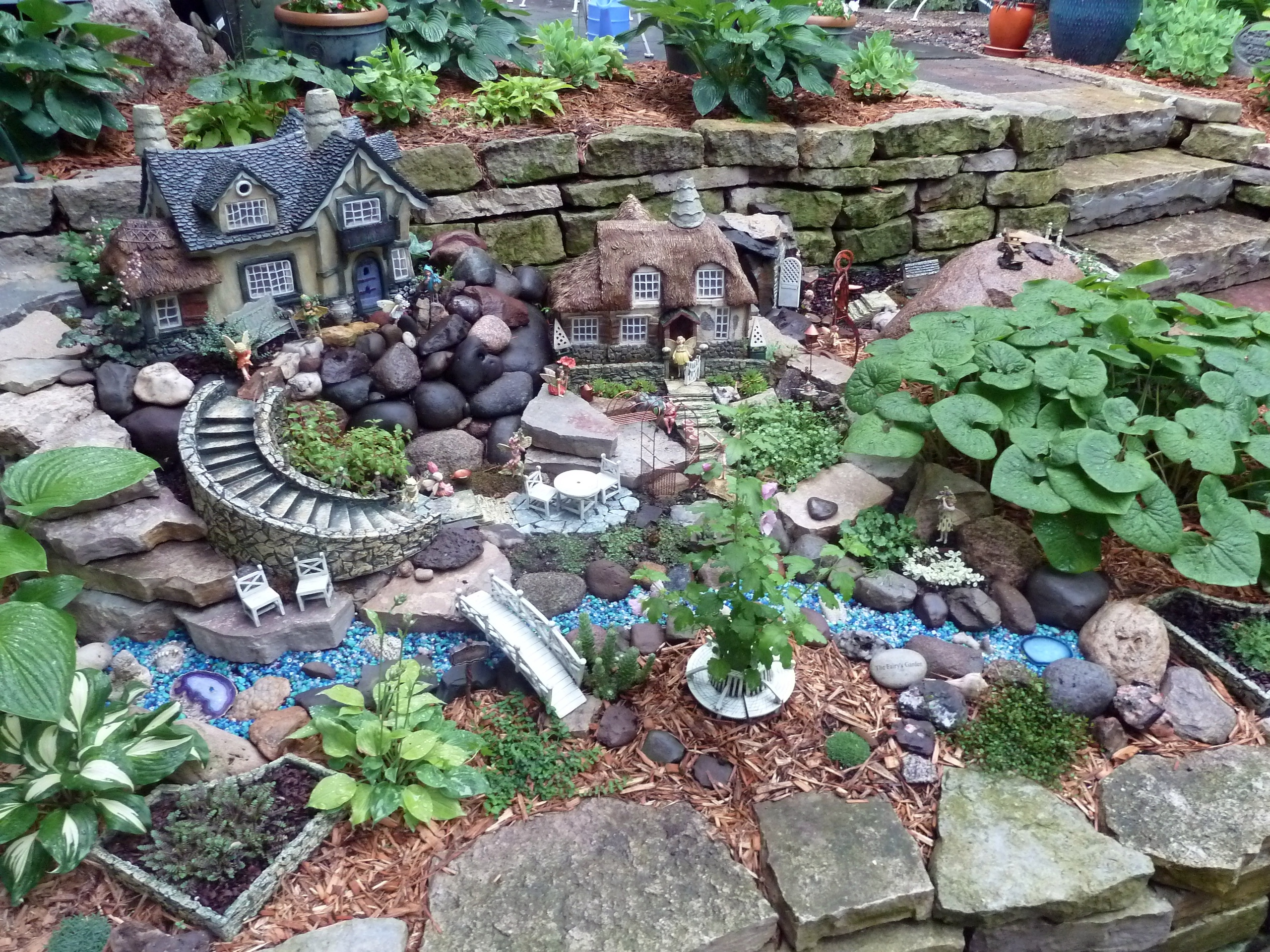 elaborate garden set up, including two fairy houses, a tiny winding staircase, several figurines and accessories, how to make a fairy garden, different kinds of plants