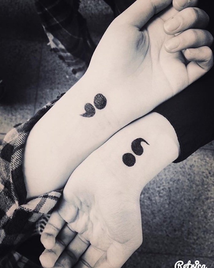 bold matching tattoos of semicolons in black, on the wrists of two hands, placed next to each other, suicide awareness tattoo
