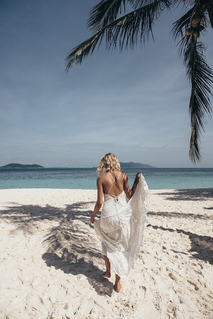 palm tree on a sandy beach, near an azure blue sea, curly blonde woman, walking towards the water, holding the skirt of her white, embroidered boho gown, beach wedding dresses