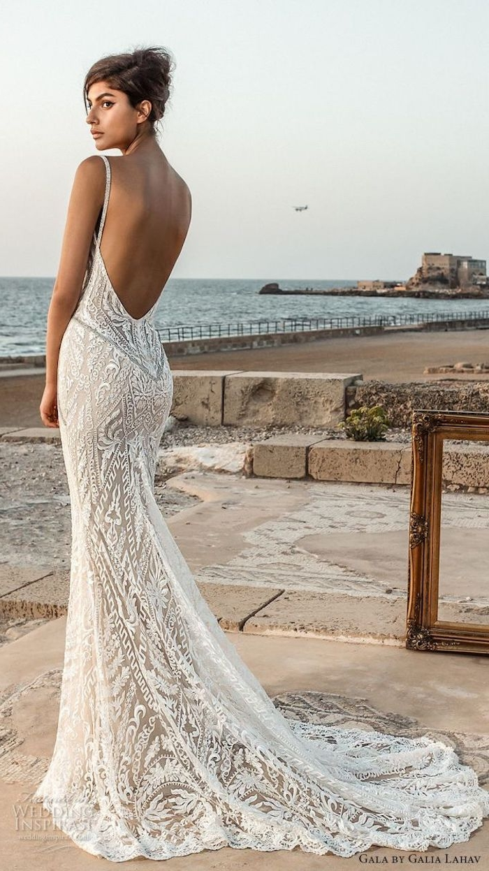 backless white and nude mermaid-style, lace beach wedding dress, worn by tanned young woman, with brunette hair in a messy bun, standing near the sea