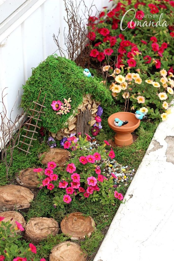 birdbath of a miniature size, placed near a diy fairy house, with moss-covered roof, and tiny ladder, in a garden with pink, red and yellow flowers