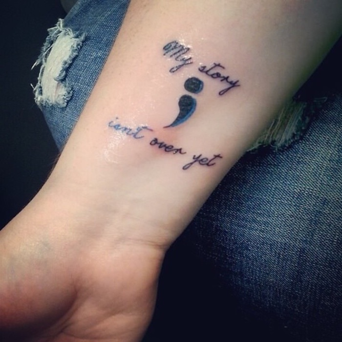 what does a semicolon tattoo mean, my story isn't over yet, written in black, with a semicolon in black and dark blue, tattooed on a person's wrist