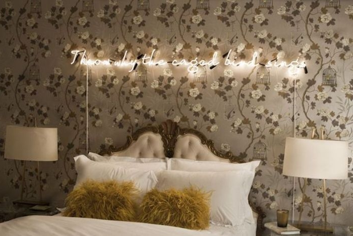 baroque style headboard, in white and gray, on plain white bed, with two fluffy yellow cushions, bedroom decorating ideas, floral wallpaper with neon writing