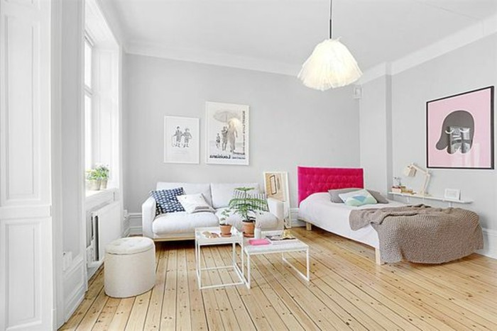 wooden floor in pale beige, inside room with white and pale gray walls, bed with hot pink board, apartment design, white sofa and two coffee tables
