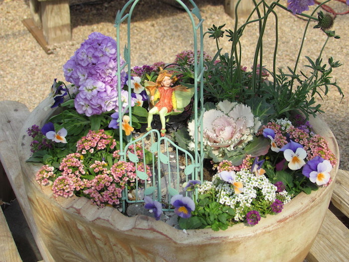 pale pink and purple flowers, with dashes of yellow, planted inside a large beige pot, decorated with a miniature blue wrought metal arch, with gates and a fairy figurine