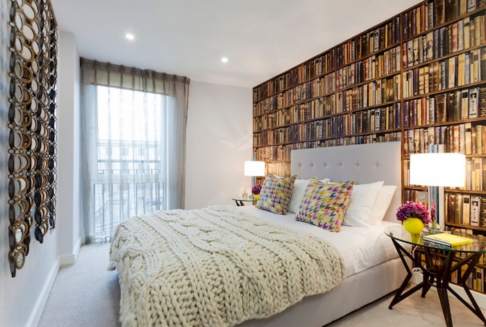 library photo wallpaper, with many different books, on a wall behind a pale gray double bed, master bedroom ideas, multi colored cushions, cream chunky knit throw