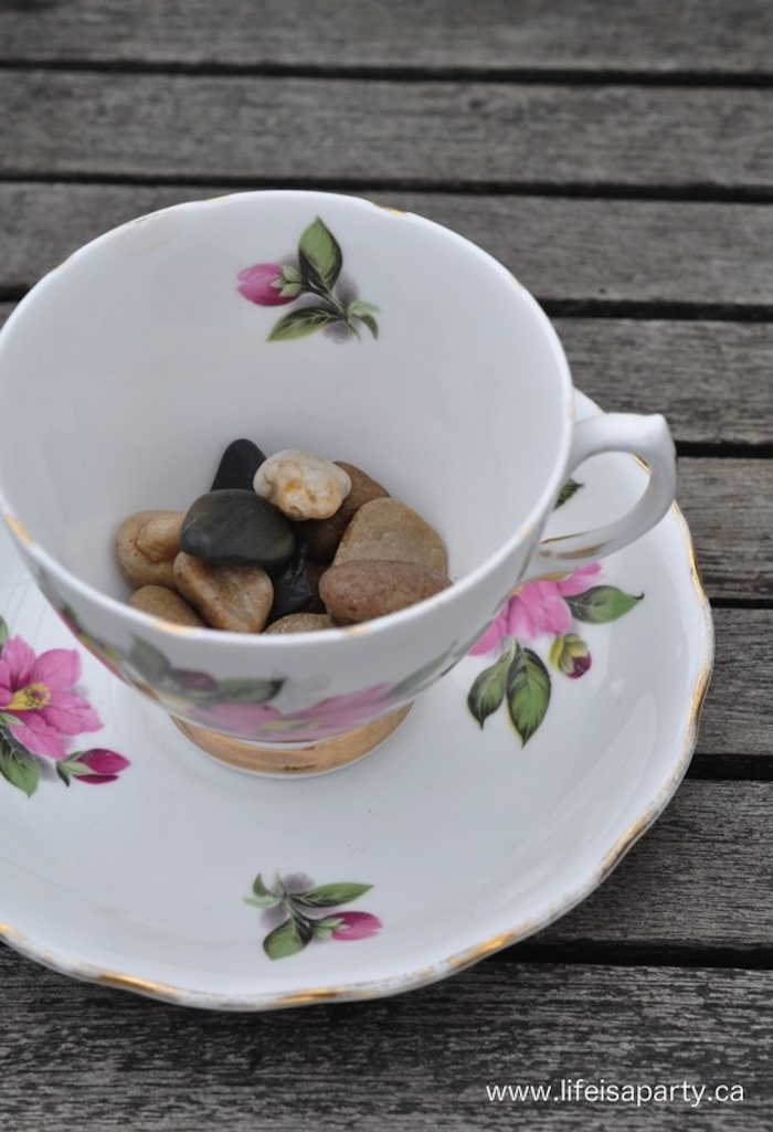 porcelain teacup in white, with a pink and green floral motive, and s matching saucer, half filled with pebbles in different colors, how to make a fairy garden