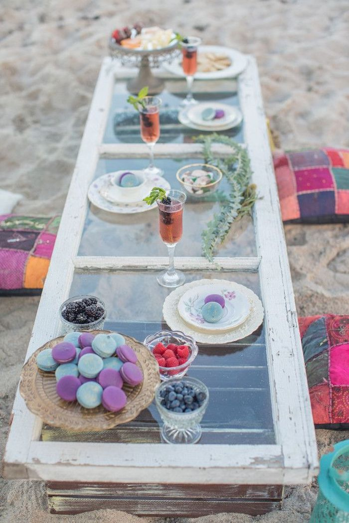 plate of macaroons, dishes with different berries, and glasses containing a pink cocktail, on a rustic outdoor table, made from a used window and two wooden crates