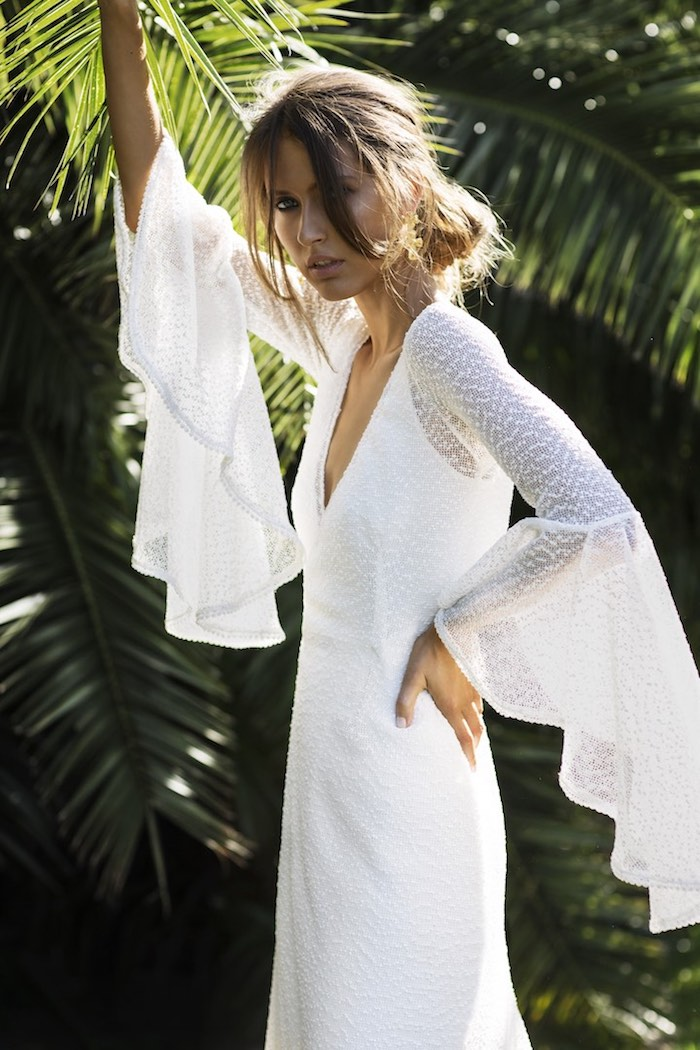flared sleeves on white, lace boho dress, inspired by the 70s, beach wedding dresses, worn by tan brunette woman, with messy hair bun, standing near palm trees
