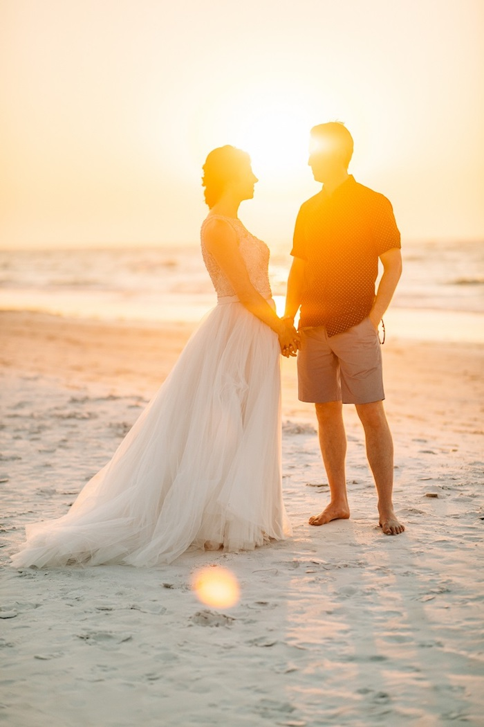 fine white sand, sea and a sunset, illuminating a couple holding hands, bride in long floaty tulle gown, groom in beige shorts, and a short-sleeved shirt, florida destination weddings