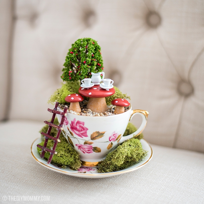 tiny white tea set, on a small mushroom table, with two matching chairs, placed in a small garden, how to make a fairy garden, with moss and a faux tree, inside a porcelain teacup