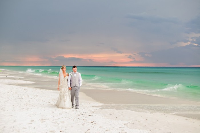 couple walking hand in hand, bride with embroidered off-white dress, and groom in grey two piece suit, sunset and white sand, beach wedding