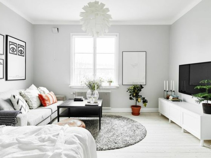 studio apartment decorating ideas, white room with round gray fluffy rug, off-white sofa with several cushions, white cupboard and large TV, lamp and coffee table